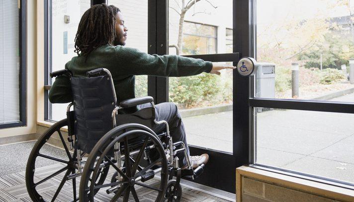 Foto de um homem em uma sala fechada. Ele está sentado em uma cadeira de rodas e ergue a mão direita em direção a um botão exisstente em uma porta à frente dele. O botão contém o símbolo universal da pessoa com deficiência.