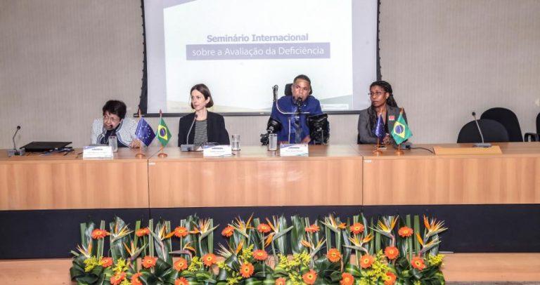 """Foto de três mulheres e um homem, cada qual com um microfone. A primeira pessoa da esquerda é Izabel Maior. Ela tem cabelos pretos e curtos e usa óculos. Todos estão sentados em frente a uma mesa. Ao fundo, uma projeção diz: """"Seminário Internacional sobre a Avaliação da Deficiência"""". À frente, há um arranjo de flores."""