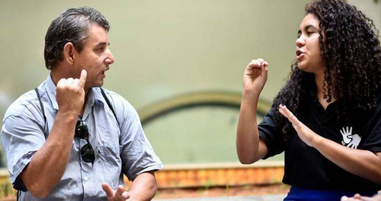 Foto de um homem e uma mulher se comunicando em LIBRAS. Ambos estão retratados da cintura para cima. O homem está à esquerda, tem cabelos grissalhos, é branco e usa uma camisa azul. A mulher, à direita, tem cabelo cacheado, pele de cor parda e usa uma camiseta preta com o sinal de LIBRAS.