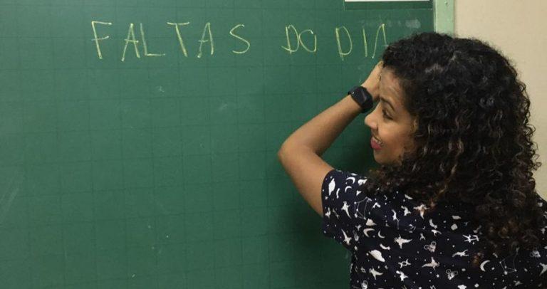 """Em uma sala de aula, uma professora escreve em um quadro negro as palavras """"faltas do dia"""". Ela tem cabelos pretos encaracolados e usa uma blusa preta."""