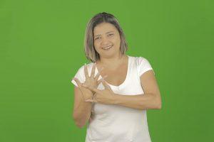 Michele faz sinal de Libras em fundo verde. Ela tem cabelos curtos e loiros e veste uma blusa branca.