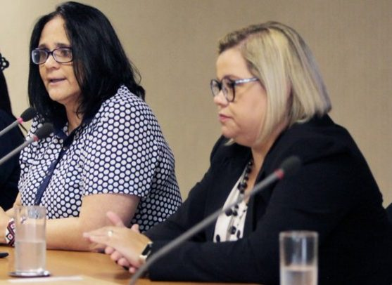 Damares Alves e Priscilla Gaspar estão sentadas, lado a lado, durante evento oficial.