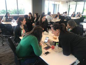 Foto dos convidados divididos em seis grupos, cada qual em uma mesa de trabalho. Os grupos estão absortos em discussões. A sala é ampla e, para além das paredes envidraçadas, há um jardim de plantas tropicais.