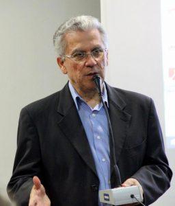 Foto de Heleno Rodrigues Corrêa Filho, da cintura para cima. Ele segura um microfone. Usa terno preto e camisa azul. Ao fundo, há uma parede branca.