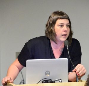 Foto de Patrícia Pavanelli, da cintura para cima. Ela fala em frente a um notebook, que está apoiado em um púlpito.
