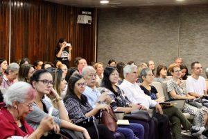 Foto da plateia no auditório da Superintendência Regional do Trabalho. O auditório está lotado, com cerca de 100 pessoas sentadas.