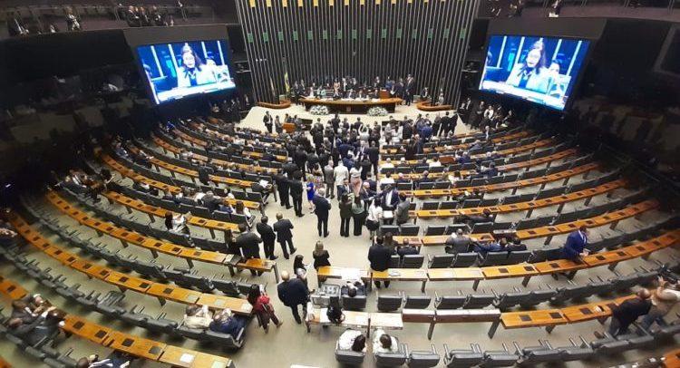 Foto de dentro da plenária. Deputados conversam no corredor, entre as fileiras de mesas.