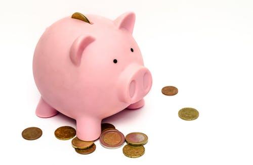 Ilustração de um cofre em forma de porquinho. Ele é rosa e está em cima de uma mesa, na qual também estão algumas moedas.