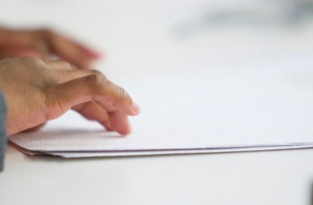 Foto parcialmente incolor da mão de uma mulher lendo uma folha com escrita em Braille. A folha e parte da mesa são brancas.