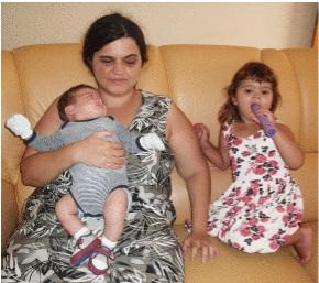 Foto de Joyce Guerra. Ela está sentada em um sofá e segura um bebê no colo. À direita dela, de joelhos no sofá, está uma menina com cerca de três anos de idade. Joyce tem pele parda, cabelo preto, longo e ondulado, que está preso. Ela usa um vestido preto com detalhes brancos.