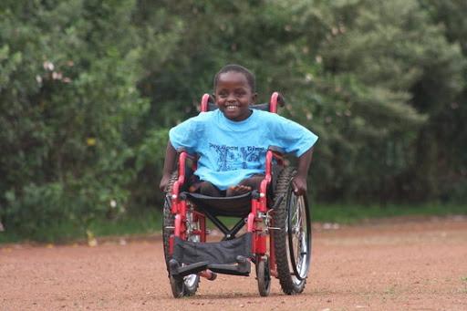 Criança sorrindo, conduzindo sua cadeira de rodas manual por uma rua sem pavimentação, com arbustos na margem.