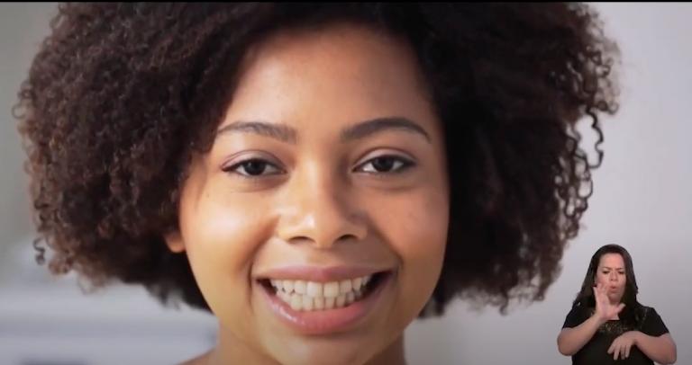 close do rosto de uma mulher jovem sorrindo, de cabelos crespos e pele negra. ao seu lado aparece uma intérprete de Libras.