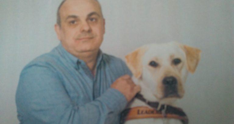 Marcelo Panico posa para foto ao lado do seu cão-guia Rudy. Marcelo tem 51 anos de idade, é branco, usa camisa de mangas compridas de cor azul. Rudy é um cão labrador branco, está com coleira marrom.