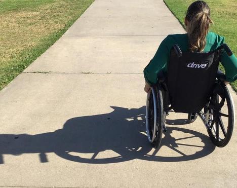uma mulher está sentada em uma cadeira de rodas, e aparece de costas, com os cabelos castanhos amarrados. Ela usa uma blusa verde de mangas compridas e está em uma calçada plana, com grama baixa dos dois lados. É possível ver a sombra da cadeira no chão.