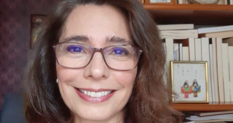 Imagem da Dra. Adriane Reis de Araújo. Ela é uma mulher branca, com cabelos escuros na altura do ombro,olhos escuros, usa óculos e está sorrindo. Está vestindo uma blusa azul sob um casaco vermelho e usa uma corrente com um pingente . Ao fundo, há uma estante de livros.