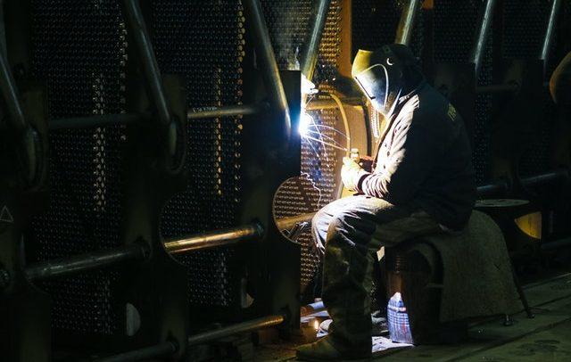 Homem em ambiente de indústria metalúrgica utiliza uniforme e capacetr. Ele está sentado e aponta um foco de luz para o local onde está realizando uma solda