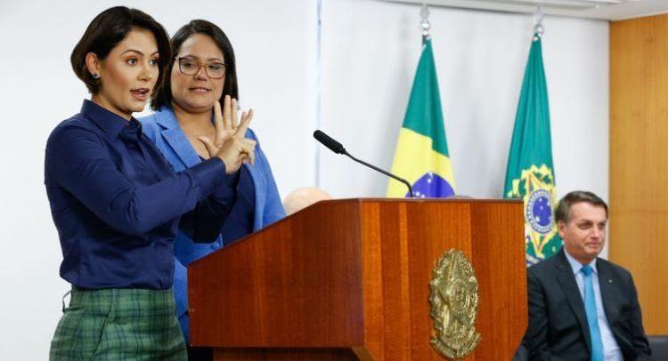 Primeira-dama Michelle Bolsonaro faz discurso em LIBRAS, em um púlpito de madeira com o brasão do governo federal. Michelle é uma mulher branca, de cabelos curtos pretos, olhos escuros, veste uma camisa azul e uma saia xadrez verde. Ao seu lado está uma mulher branca, cabelos pretos curtos e veste um casaco azul. Ao lado, está sentado em uma cadeira o presidente Jair Bolsonaro. Atrás, é possível ver as bandeiras do Brasil e da independência