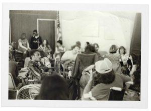 foto em preto e branco mostrando diversos cadeirantes e brad lomax aparece de lado