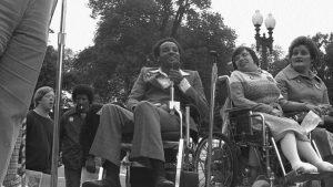 foto em preto e branco mostra Brad Lomax em uma cadeira de rodas, segurando um microfone. Ele é negro e veste calça e paletó cinza. Ao seu lado, estão duas mulheres, também na cadeira de rodas. Eles estão em um ambiente arborizado.