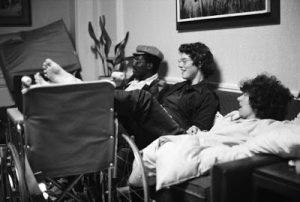 foto em preto e branco mostra três homens sentados num sofá, com os pés esticados em uma cadeira de rodas.