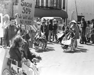 foto preto e branco de manifestantes cadeirantes reunidos na rua.