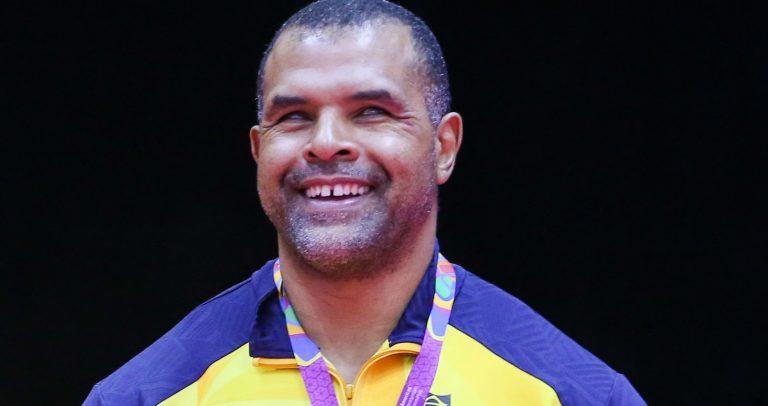 Antonio Tenório é um homem negro, de cabelos curtos e grisalhos. Ele usa uma camisa amarela com uma faixa azul nos ombros e gola azul. No peito, tem uma pequena imagem da bandeira do Brasil. Ele está sorrindo.
