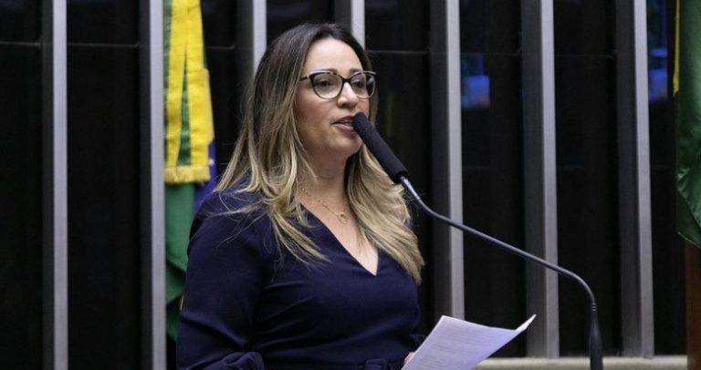 Foto da deputada Rejane Dias. Ela é uma mulher branca, de cabelos loiros e longos, usa óculos. Usa uma blusa preta de manga longa. e está falando em um púlpito com microfone.