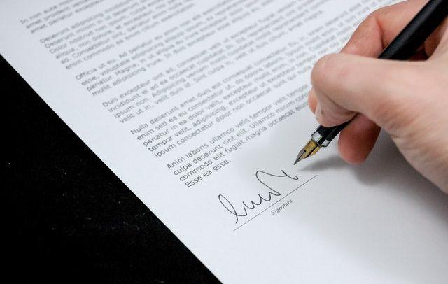 A foto detalha a mão de uma pessoa assinando um documento com uma caneta de cor preta.