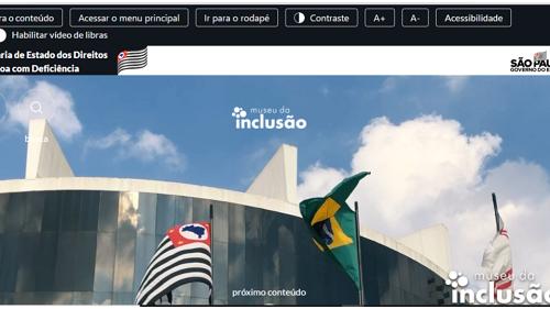 """Reprodução da página principal do site do Museu da Inclusão. Na barra superior, há botões """"ir para o conteúdo"""", """"acessar o menu principal"""", ir para o rodapé"""", """"contraste A+ A-, """"Acessibiildade. Abaixo, há o botão escrito """"habilitar vídeo de libras"""" e o título Secretaria do Estado dos Direitos da pessoa com deficiência, junto à bandeira de São Paulo. Abaixo, há uma foto detalhando um céu azul e nuvens brancas, e um pedaço da parte superior da fachada do Memorial da América Latina, onde se localiza o Museu da Inclusão. Há 3 bandeiras hasteadas. No canto direito, há o logo do memorial da Inclusão"""