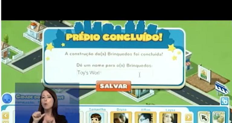 tela de um game, em um fundo verde há uma mensagem escrita: prédio concluído: A construção dos brinquedos foi concluída. No canto esquerdo, há uma mulher fazendo a interpretação de libras, ap lado há quatro figuras de avatares do jogo