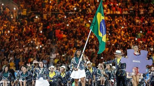 imagem da delegação brasileira no evento de abertura das Olimpíadas Rio-2016. em primeiro plano, a delegação de atletas paralímpicos e uma atleta negra carrega a bandeira do Brasil. Ela veste o uniforme composto por um casaco verde escuro e uma saia curta branca.