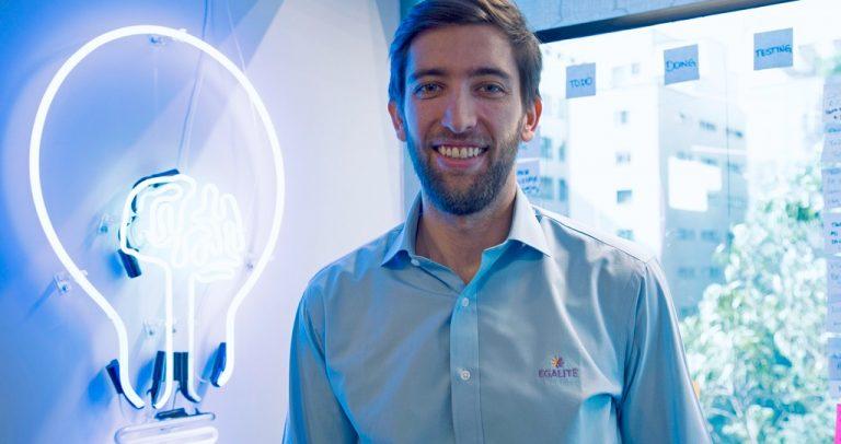 Guilherme Braga, CEO da Egalitê, é um homem branco, de olhos azuis, de cabelos castanhos claros curtos e barba. Ele usa uma camisa social azul clara com o logo da Egalitê do lado esquerdo. Atrás dele, há uma parede no mesmo tom, com o desenho de uma lâmpada acesa em luzes de neon.